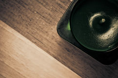 Scented candle in a glass. Green scented candle in a glass on a wood surface Stock Images