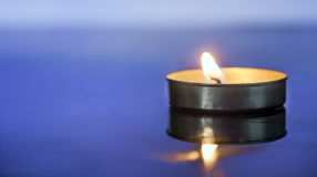 Scented Candle light over blue background Royalty Free Stock Images