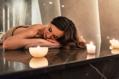 Scented candle next to young woman on marble massage table at sp. Scented round candle  next to young woman on marble massage table during aromatherapy at luxury Stock Images