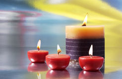 Scented candles. Three small red candles and a large candle on background nuanced royalty free stock images