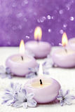 Scented candles and hyacinth flowers on violet background Stock Images