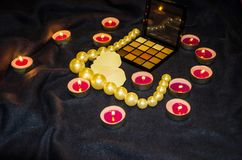 Scented candles, a palette of shadows, a heart and beautiful beads on a blanket stock photo