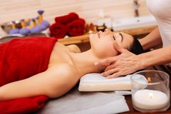Tranquil sleepy woman covered with red towel on massage table stock images