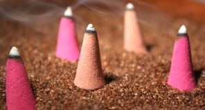 Scented cones on sand. Five incense cones (brown and pink ones) burning on brown sand, focus on central one, smoke floating all around Royalty Free Stock Photography