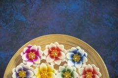 Scented flower candles. On wooden tray with copy space stock photos