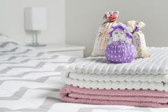 Scented sachets and fragrant pouch figure of a girl. Bags filled with lavender in bedroom. Towels on bed. royalty free stock image