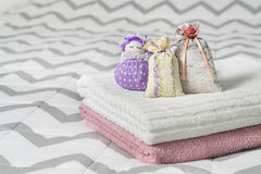 Scented sachets and fragrant pouch figure of a girl. Bags filled with lavender in bedroom. Towels on bed. royalty free stock photos