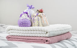 Scented sachets and purple lavender pouch figure of a girl. Nice smelling bags in bedroom. Towels on bed. royalty free stock photo
