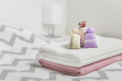 Scented sachets on towels on bed. Fragrant pouches for cozy home. Dried lavender in decoration bags in bedroom. Furnishing accessories and light color Stock Photos