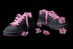 Scented sneakers. Sneakers with flowers scattered around royalty free stock photo
