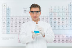 Scentist presenting a discovery. Close-up of handsome male scientist smiling and holding a flask with blue substance, with periodic table in background, in a Royalty Free Stock Images