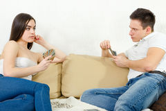 Sceptic young couple cheating each other in card game Stock Image