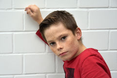 Sceptical looking teenager boy. Portrait of a sceptical looking teenager boy leaning at a wall Stock Photo