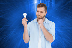 Sceptical model holding a bulb Stock Image