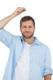 Sceptical model holding a bulb above his head and looking at cam Stock Photography