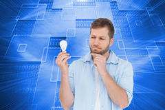 Sceptical model holding a bulb Royalty Free Stock Photos