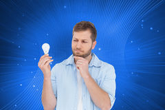 Sceptical model holding a bulb Royalty Free Stock Photo