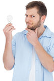 Sceptical model holding a bulb and looking at camera Royalty Free Stock Images