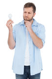 Sceptical model holding a bulb Stock Photo