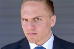 Sceptical young man glaring at camera. Sceptical young businessman glaring at camera with an intense stare and irate frown in a close up cropped head shot Stock Photos