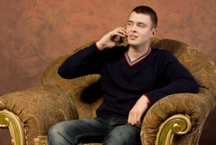 Sceptical young man talking on his mobile Royalty Free Stock Photo