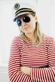 Sceptically młoda kobieta żeglarz w kapitan nakrętce - będący ubranym czerwone przerwy ubiera zdjęcie stock