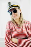 Sceptically young woman sailor in captain cap - wearing red gaps dress stock photo