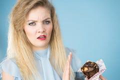 Sceptische de chocolade cupcake muffin van de vrouwenholding stock foto