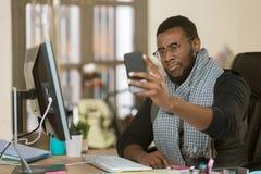 Sceptische Mens in een Bureau die Mobiel Apparaat met behulp van royalty-vrije stock foto's