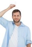 Sceptyczny model trzyma żarówkę nad jego głowa i patrzeje krzywka Fotografia Stock