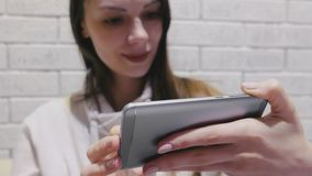 Schöne brunette Frau, die eine Serie in den Kopfhörern am Handy auf einem weißen Wandhintergrund des Ziegelsteines aufpasst stock footage