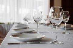 Schöne Gläser auf weißem Hintergrund des Tabellenlichtes stockfoto
