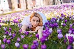 Schöne junge Blondine mit dem blauen Augen- und weißemkleid, das auf dem Teppich unter den Frühlingsblumenkrokussen liegt stockfotos