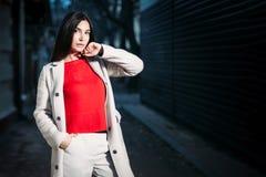 Schöne junge brunette Frau im weißen Mantel der roten Bluse, der draußen glättet lizenzfreies stockfoto