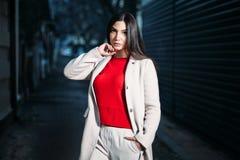 Schöne junge brunette Frau im weißen Mantel der roten Bluse, der draußen glättet lizenzfreie stockbilder