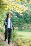 Schöne junge Frau, die entlang dem See in einem Wald wandert lizenzfreie stockfotos