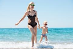 Schöne junge Mutter und kleines Sohnhändchenhalten, die auf den Wellen auf dem Strand läuft Spaß, Familie, freundliche Sommerferi stockfotos