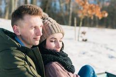 Schöne junge Paare in der Liebe, die auf einer Parkbank an einem klaren sonnigen Tag sitzt Der Junge und das Mädchen genießen die stockfoto