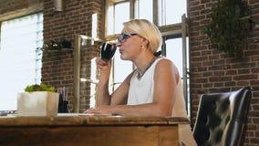 Schöne kaukasische erwachsene Frau hält eine Schale mit heißem Kaffee während Arbeiten am Arbeitsplatz Geschäftsfrau, die herein  stock footage