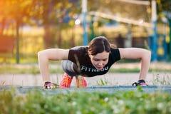 Schöner dünner Brunette, der irgendeine Stoß-UPS-Außenseite im Park tut Eignungsfrau während Quertrainingstrainings des im Freien lizenzfreie stockfotos