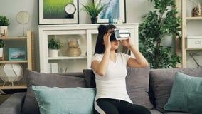 Schöner dunkelhaariger Brunette hat Spaß mit Gläsern beweglicher Kopf und die Hände der virtuellen Realität, die Kopfhörer tragen stock footage