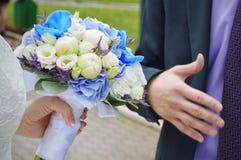 Schöner Hochzeitsblumenstrauß in den Händen der Braut stockfotografie