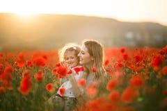 Schönes lächelndes Baby mit Mutter haben Spaß auf dem Gebiet von roten Mohnblumenblumen über Sonnenunterganglichtern, Frühlingsze stockfotografie