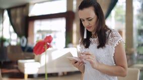 Schönheit, die eine Tablette in einer Hotellobby sitzt verwendet, einen Tasse Kaffee genießend auf einer aufwändigen lächelnden C stock footage