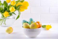 Schüssel mit bunten Ostereiern, Frühlingsostern-Dekoration auf weißem Holztisch mit Blumenstrauß von gelben Tulpenblumen im Glasv lizenzfreie stockbilder