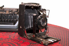 Schäbige alte Fotokamera und -schreibmaschine auf der roten Tischdecken-ISO Lizenzfreies Stockfoto