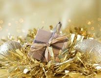 Schäbige schicke Geschenkbox schmiegte sich in der Goldweihnachtsgirlande an Stockfoto