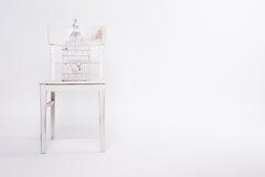 Schäbiger Stuhl mit Birdcage Stockfotografie