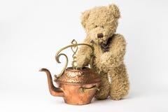 Schäbiger Teddybär mit kupfernem Kessel auf weißem Hintergrund Stockbilder