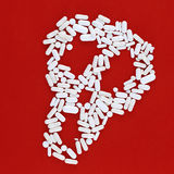 Schädel hergestellt von den weißen Pillen auf einem roten Hintergrund Lizenzfreie Stockfotos